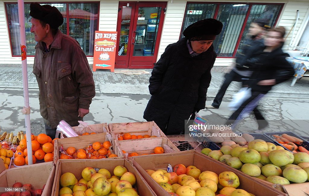 A Kyrgyz woman looks at fruit for sale in Bishkek the capital of the Central Asian state of Kyrgyzstan on February 18 2011 AFP PHOTO/ VYACHESLAV...