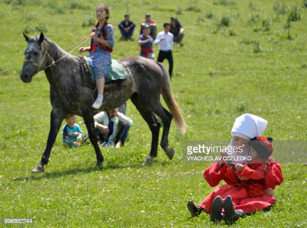 Kyrgyz woman wearing a traditional dress plays with a child during a folk festival at Kyrgyzstan's ChonKurchak valley some 30km outside Bishkek on...