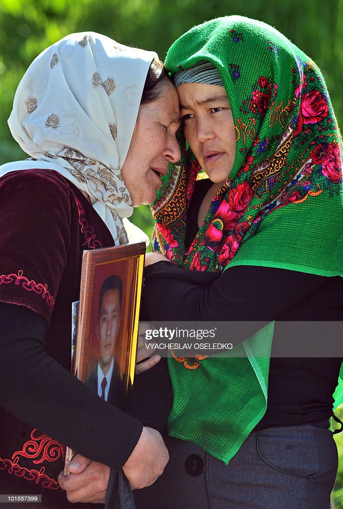 Kyrgyz women cry as they hold a picture of their relative killed during the unrest at Ata-Beyit cemetery some 20km outside Bishkek on May 12, 2010. In late April, Kyrgyzstan's interim government said it had charged ousted president Kurmanbek Bakiyev with mass killings and asked Belarus to hand him over for trial.
