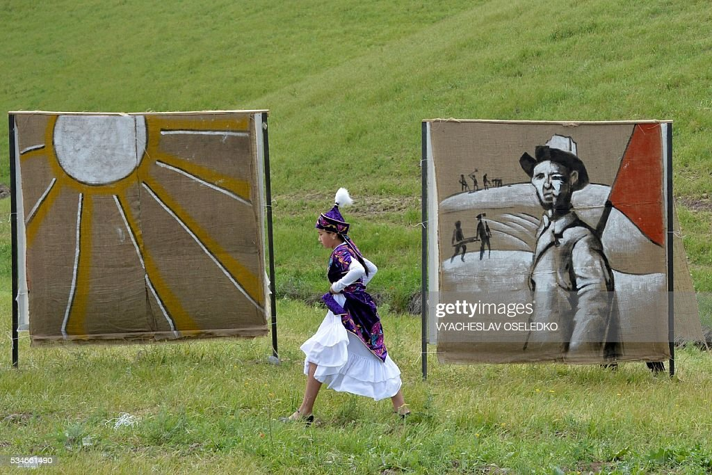 A Kyrgyz women in traditional costume lifts her skirt as she walks through mud during the celebrations of the 90th anniversary formation of the Chui region in the village of Kuntu some 20 kms from Bishkek on May 27, 2016. / AFP / VYACHESLAV