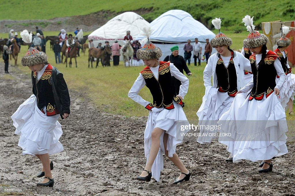 Kyrgyz women in traditional costumes lift their skirts as they walk through mud during the celebrations of the 90th anniversary formation of the Chui region in the village of Kuntu some 20 kms from Bishkek on May 27, 2016. / AFP / VYACHESLAV