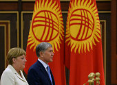 Kyrgyzstan's President Almazbek Atambayev and German Chancellor Angela Merkel take part in an official welcoming ceremony at the airport of Manas...