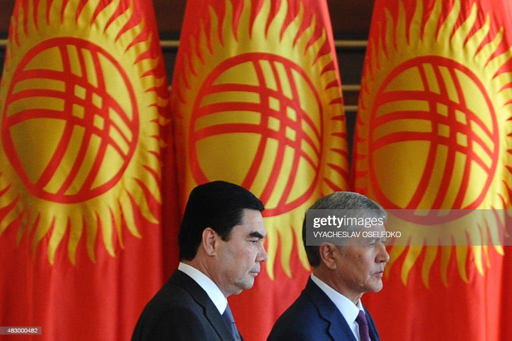 Kyrgyzstan's President Almazbek Atambayev and Turkmenistan's President Gurbanguly Berdymukhamedov walk past Kyrgyz flags during an official welcoming...