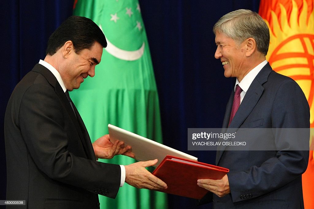 Kyrgyzstan's President Almazbek Atambayev (R) and Turkmenistan's President Gurbanguly Berdymukhamedov exchange documents during a signing ceremony at the Ala-Archa state residence in Bishkek on August 5, 2015.