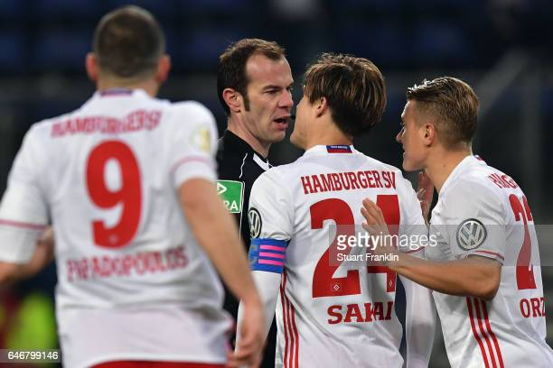 Kyriakos Papadopoulos Gotoku Sakai and Matthias Ostrzolek of Hamburg discuss with referee Marco Fritz during the DFB Cup quarter final between...