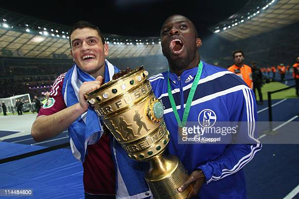 Kyriakos Papadopoulos of Schalke and Hans Sarpei of Schalke lift the DFB Cup trophy following his team's victory at the end of the the DFB Cup final...