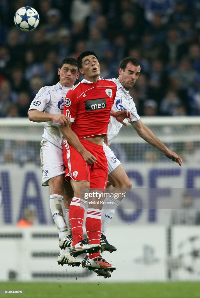 Kyriakos Papadopoulos of Schalke, Oscar Cardozo of Benfica and Christoph Metzelder of Schalke go up for a header during the UEFA Champions League match between FC Schalke 04 and SL Benfica at Veltins Arena on September 29, 2010 in Gelsenkirchen, Germany.