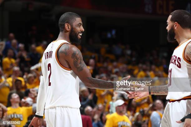 Kyrie Irving and Deron Williams of the Cleveland Cavaliers give five against the Toronto Raptors in Game One of the Eastern Conference Semifinals of...