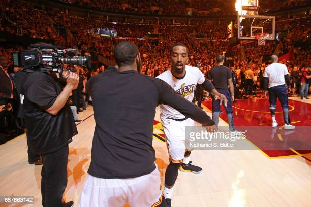 Kyrie Irving and JR Smith of the Cleveland Cavaliers shake hands before Game Four of the Eastern Conference Finals against the Boston Celtics during...