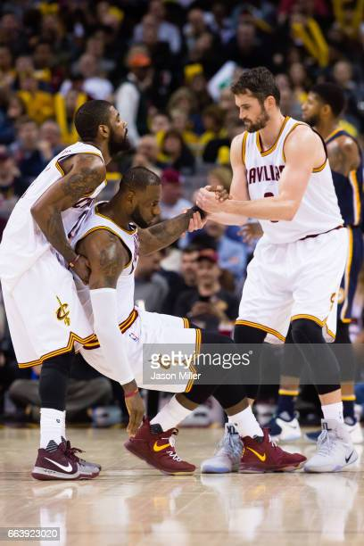 Kyrie Irving and Kevin Love of the Cleveland Cavaliers help LeBron James of the Cleveland Cavaliers to his feet after James was fouled during the...