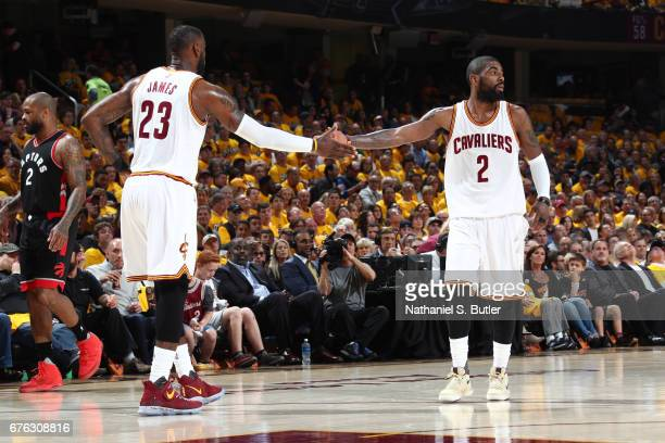 Kyrie Irving and LeBron James of the Cleveland Cavaliers high five against the Toronto Raptors in Game One of the Eastern Conference Semifinals of...