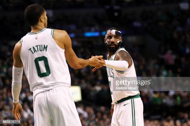 Kyrie Irving of the Boston Celtics congratulates Jayson Tatum after he scored against the Philadelphia 76ers during the second quarter at TD Garden...
