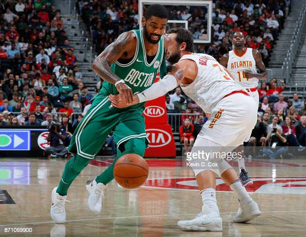 Kyrie Irving of the Boston Celtics draws a foul from Marco Belinelli of the Atlanta Hawks at Philips Arena on November 6 2017 in Atlanta Georgia NOTE...