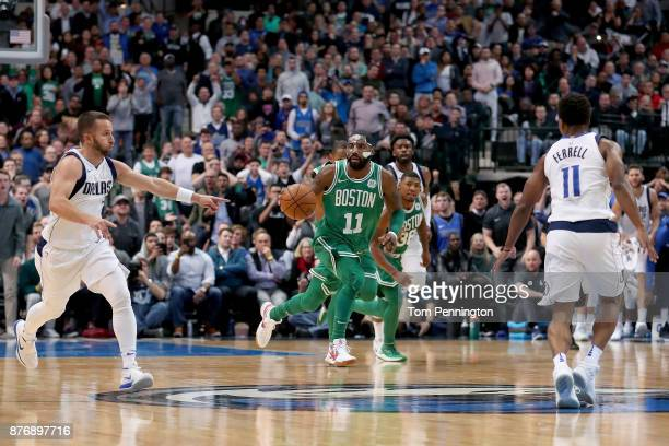 Kyrie Irving of the Boston Celtics dribbles the ball against JJ Barea of the Dallas Mavericks and Yogi Ferrell of the Dallas Mavericks at American...