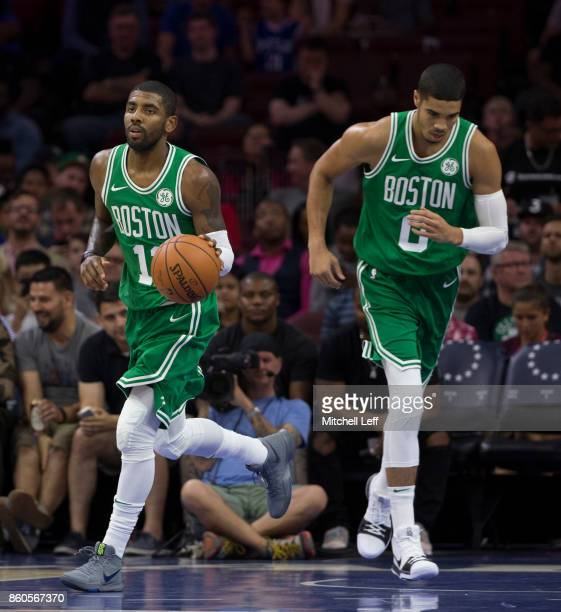 Kyrie Irving of the Boston Celtics dribbles the ball as Jayson Tatum heads up the court against the Philadelphia 76ers at the Wells Fargo Center on...
