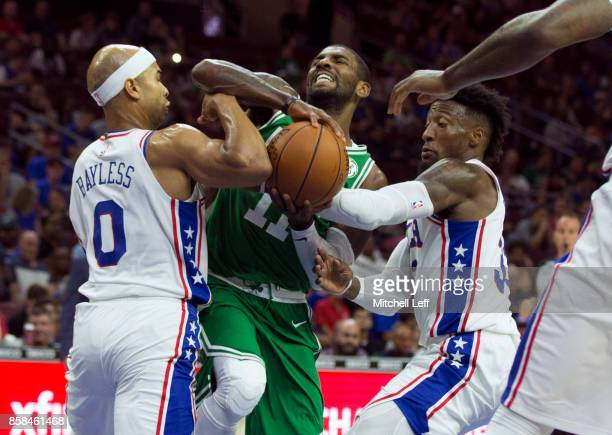 Kyrie Irving of the Boston Celtics drives to the basket in the first quarter of the preseason game against Jerryd Bayless and Robert Covington of the...