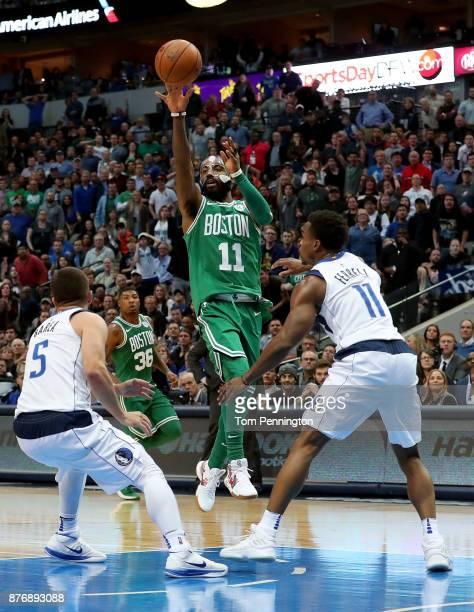 Kyrie Irving of the Boston Celtics shoots the ball against JJ Barea of the Dallas Mavericks and Yogi Ferrell of the Dallas Mavericks at American...