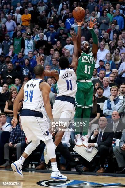 Kyrie Irving of the Boston Celtics shoots the ball against Yogi Ferrell of the Dallas Mavericks and Devin Harris of the Dallas Mavericks at American...