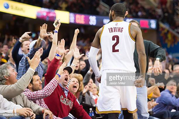 Kyrie Irving of the Cleveland Cavaliers celebrates with fans after scoring and being fouled during the second half against the Milwaukee Bucks at...