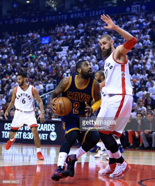 Kyrie Irving of the Cleveland Cavaliers dribbles the ball as Jonas Valanciunas of the Toronto Raptors defends in the first half of Game Four of the...