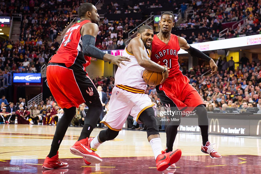 Kyrie Irving #2 of the Cleveland Cavaliers drives between Patrick Patterson #54 and Terrence Ross #31 of the Toronto Raptors during the second half at Quicken Loans Arena on December 9, 2014 in Cleveland, Ohio. The Cavaliers defeated the Raptors 105-101.