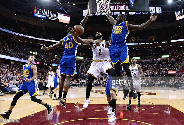 Kyrie Irving of the Cleveland Cavaliers drives to the basket against Harrison Barnes of the Golden State Warriors and Draymond Green during the...
