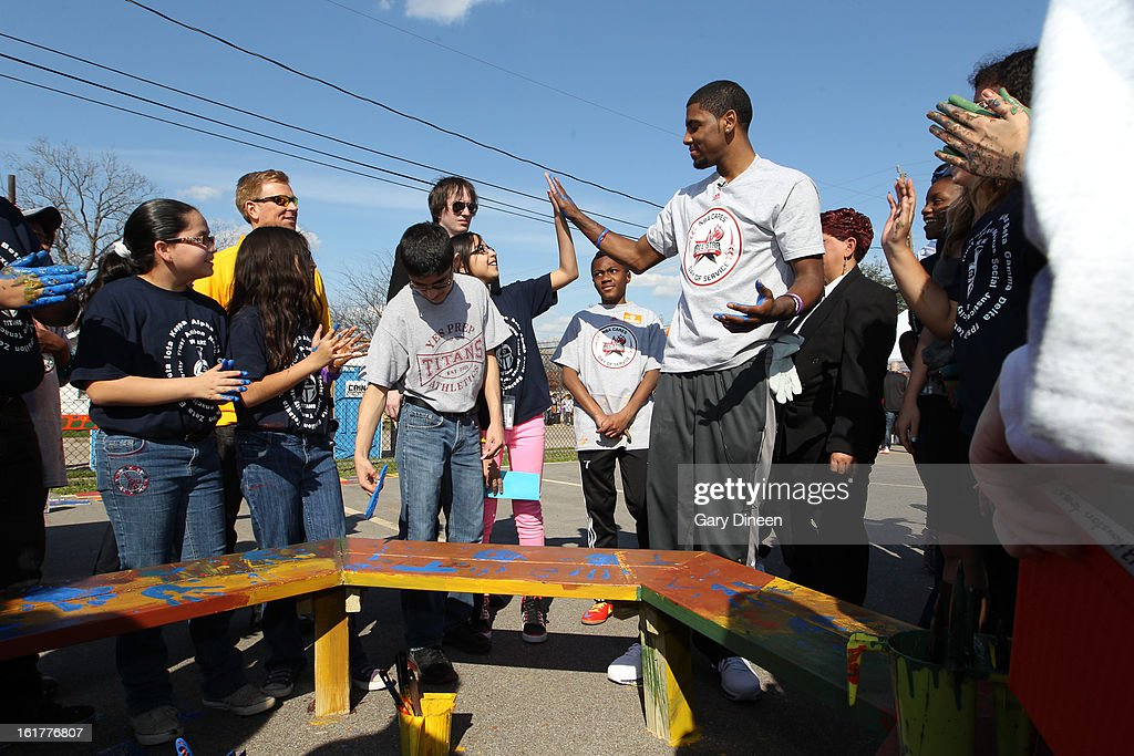 Kyrie Irving #2 of the Cleveland Cavaliers gives a girl a highfive while painting a bench at the 2013 NBA Cares Day of Service at the Playground Build with KaBOOM! on February 15, 2013 in Houston, Texas.