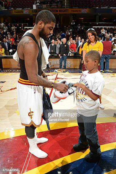 Kyrie Irving of the Cleveland Cavaliers gives his shoes away to a fan after a game against the Washington Wizards on April 15 2015 at Quicken Loans...
