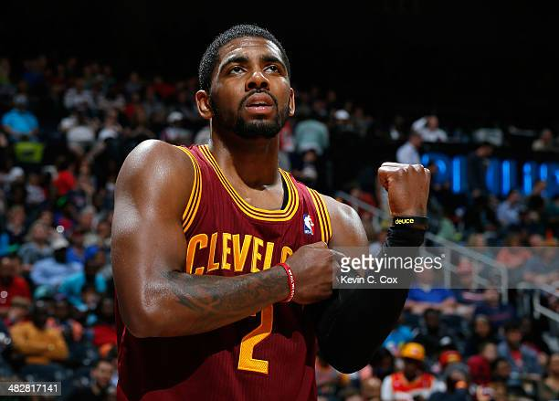 Kyrie Irving of the Cleveland Cavaliers grabs his arm after falling out of bounds with the ball against the Atlanta Hawks at Philips Arena on April 4...