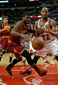 Kyrie Irving of the Cleveland Cavaliers looses control of the ball under pressure from Taj Gibson of the Chicago Bulls at the United Center on...