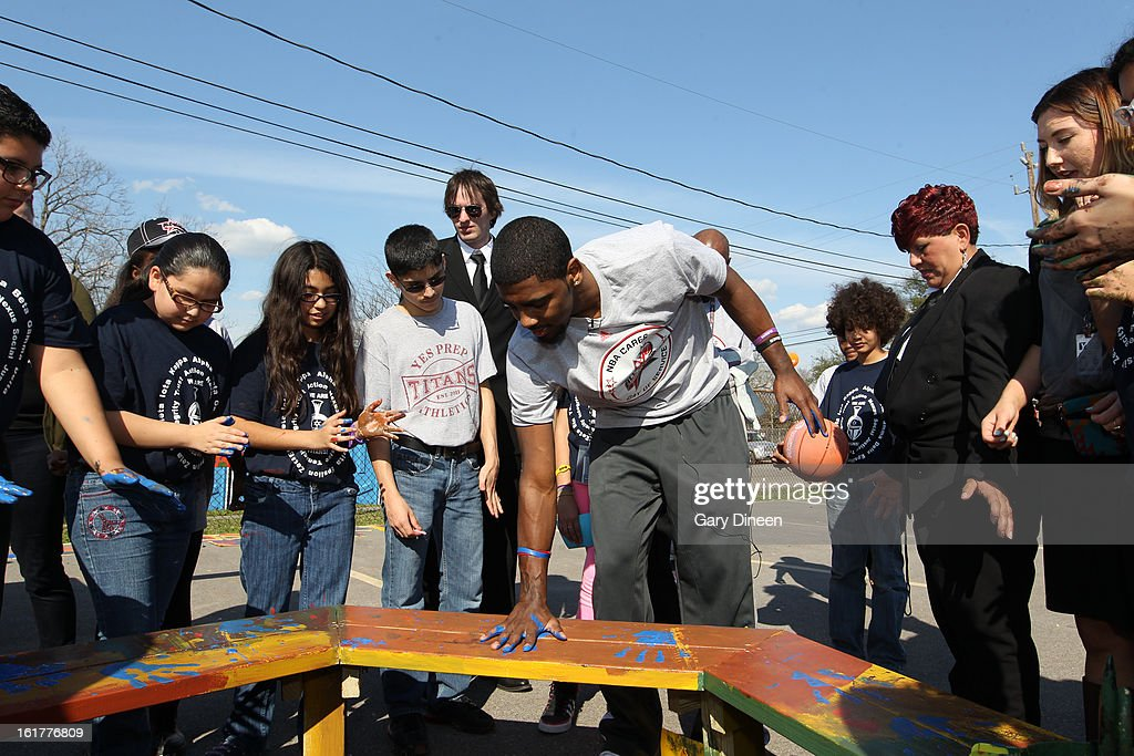 Kyrie Irving #2 of the Cleveland Cavaliers paints his hand with other kids and places it on the bench at the 2013 NBA Cares Day of Service at the Playground Build with KaBOOM! on February 15, 2013 in Houston, Texas.