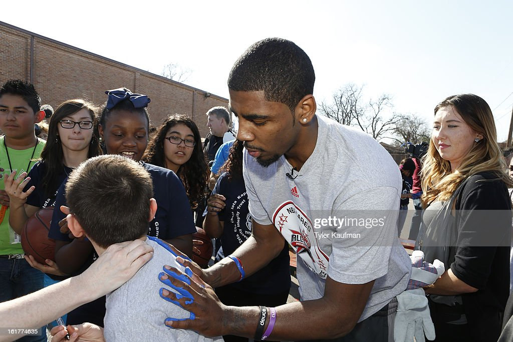 Kyrie Irving #2 of the Cleveland Cavaliers puts his hand prints on a fan's shirt at the 2013 NBA Cares Day of Service at the Playground Build with KaBOOM! on February 15, 2013 in Houston, Texas.