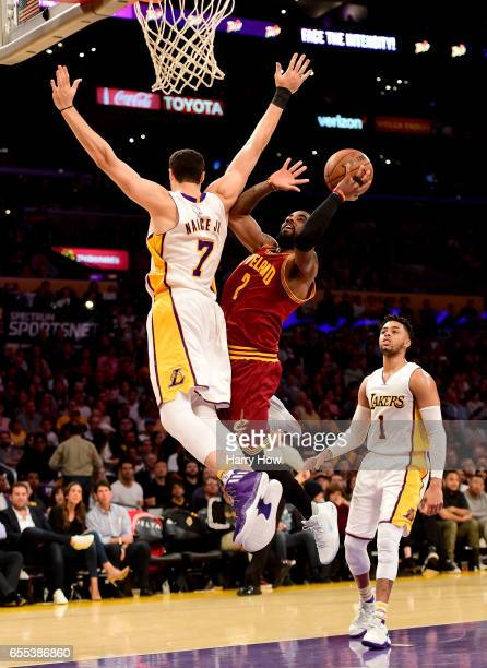 Kyrie Irving of the Cleveland Cavaliers scores on Larry Nance Jr #7 of the Los Angeles Lakers as D'Angelo Russell look on during the first half at...