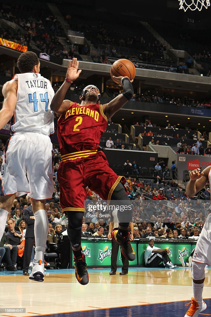 Kyrie Irving of the Cleveland Cavaliers shoots against Jeffery Taylor of the Charlotte Bobcats at the Time Warner Cable Arena on January 4 2013 in...