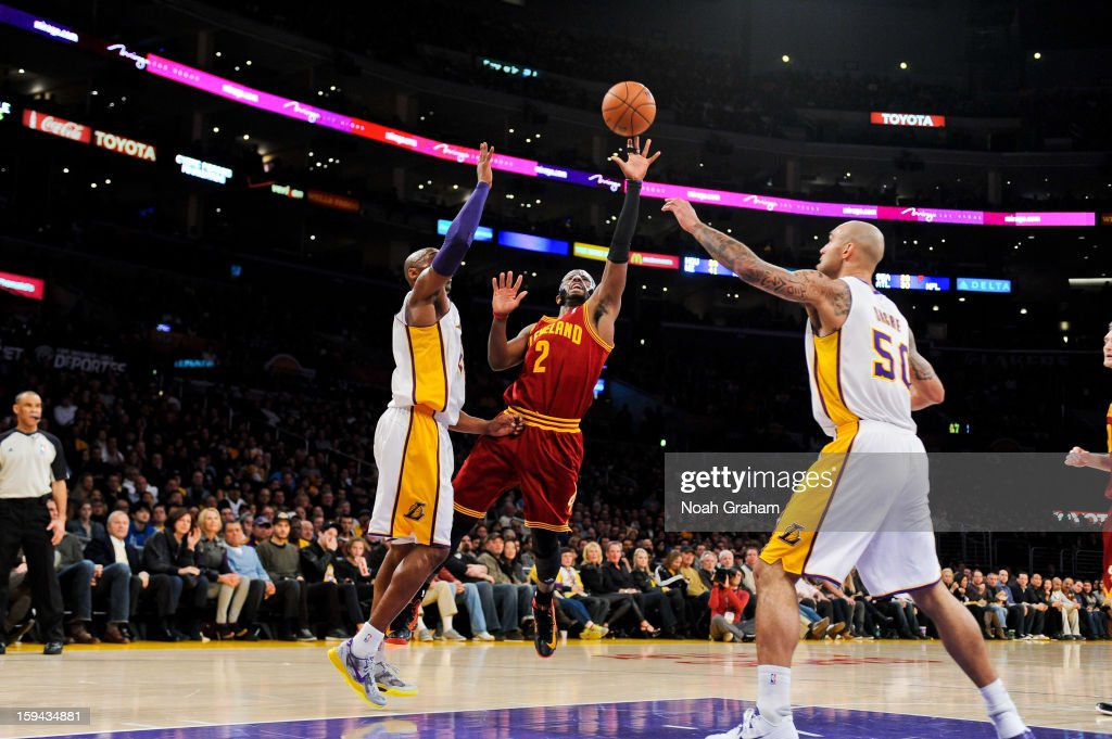 Kyrie Irving #2 of the Cleveland Cavaliers shoots in the lane against Kobe Bryant #24 and Robert Sacre #50 of the Los Angeles Lakers at Staples Center on January 13, 2013 in Los Angeles, California.