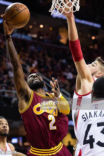 Kyrie Irving of the Cleveland Cavaliers shoots over Jonas Valanciunas and Pascal Siakam of the Toronto Raptors during the second half at Quicken...
