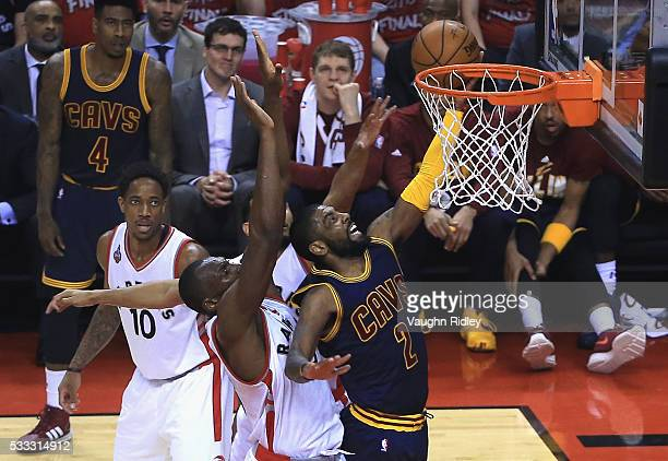 Kyrie Irving of the Cleveland Cavaliers shoots the ball against Bismack Biyombo of the Toronto Raptors during the first half in game three of the...