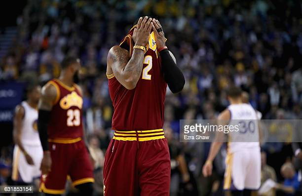 Kyrie Irving of the Cleveland Cavaliers wipes his face as he walks to the bench for a time out during their game against the Golden State Warriors at...