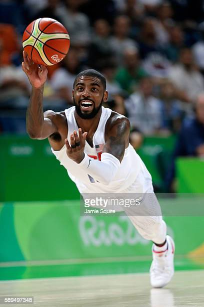 Kyrie Irving of United States passes the ball to teammate Kevin Durant not pictured #5 before falling to the court during a Men's Preliminary Round...
