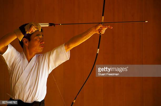 A kyudo practitioner draws his bow towards the target at the Kyoto Budo Centre dojo Kyudo is a modern Japanese martial art derived from ancient...