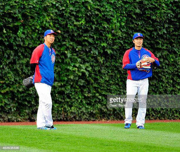 Kyuji Fujikawa of the Chicago Cubs and Tsuyoshi Wada in the outfield before the game against the Milwaukee Brewers on August 12 2014 at Wrigley Field...