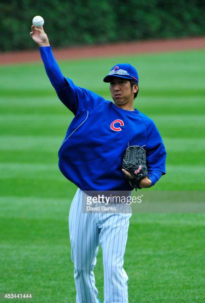 Kyuji Fujikawa of the Chicago Cubs warms up in the outfield before the game against the Tampa Bay Rays on August 10 2014 at Wrigley Field in Chicago...
