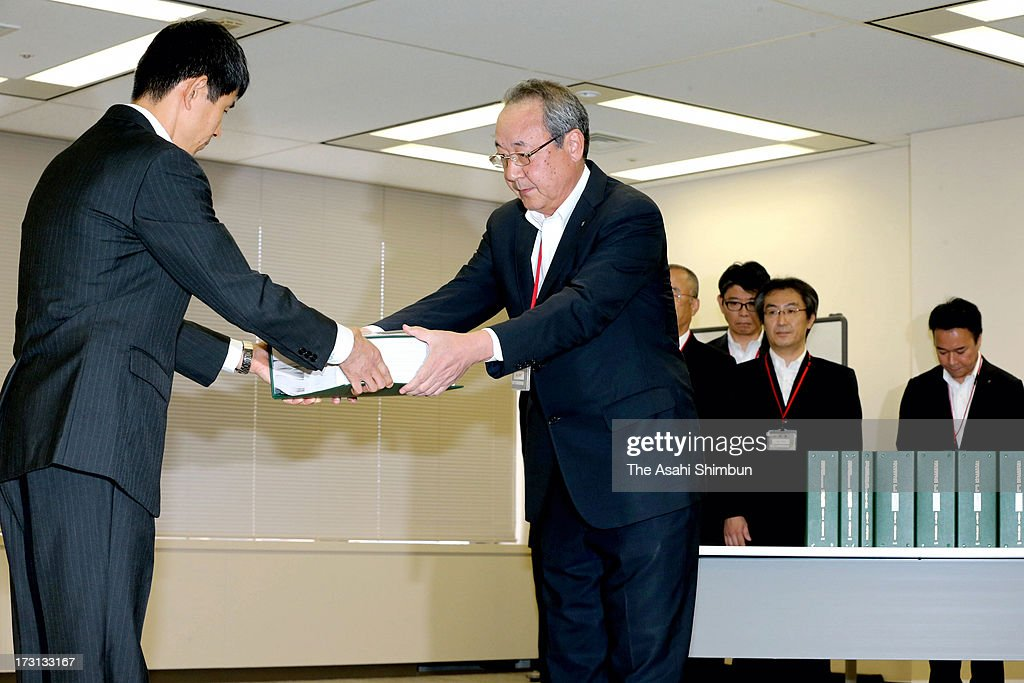 Kyushu Electric Power Co vice president Toru Yoshizako (R) hands in an application to the Nuclear Regulation Authority officer on July 8, 2013 in Tokyo, Japan. Four utilities of Hokkaido, Kansai, Shikoku and Kyushu apply for the safety examinations of ten reactors of five nuclear power plants, on the day tougher standards took effect to prevent a recurrence of the 2011 Fukushima nuclear crisis.