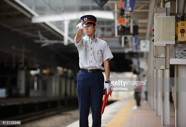 A Kyushu Railway Co employee gestures as a train departs from Hakata Station in Fukuoka Fukuoka Prefecture Japan on Tuesday Oct 11 2016JR Kyushu the...