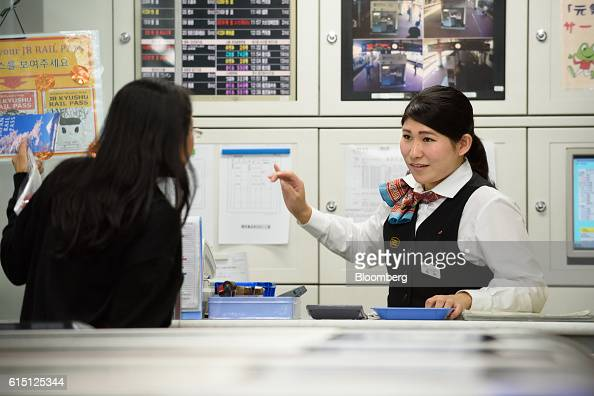 A Kyushu Railway Co employee right speaks to a passenger at a ticket counter of Hakata Station in Fukuoka Fukuoka Prefecture Japan on Tuesday Oct 11...