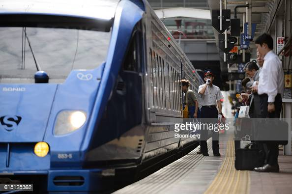 A Kyushu Railway Co employee speaks over a wireless microphone next to a 883 series Sonic limited express service train at Hakata Station in Fukuoka...