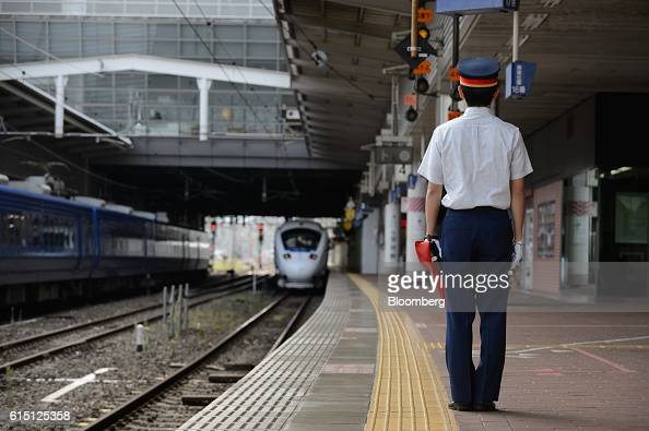 A Kyushu Railway Co employee stands as one of the company's 885 series Kamome limited express service train departs from Hakata Station in Fukuoka...