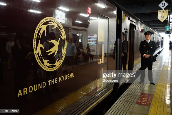 A Kyushu Railway Co employee waits for passengers outside the company's Seven Stars in Kyushu luxury train at Hakata Station in Fukuoka Japan on...