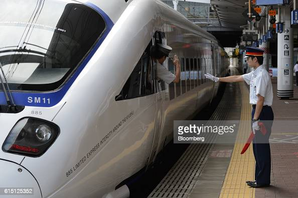 Kyushu Railway Co employees gesture as one of the company's 885 series Kamome limited express service train departs from Hakata Station in Fukuoka...