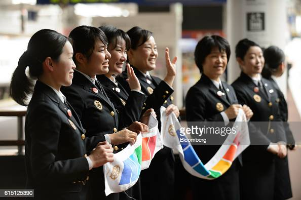 Kyushu Railway Co employees hold banners as they wave off the company's Seven Stars in Kyushu luxury train not pictured at Hakata Station in Fukuoka...